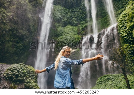Rear view of happy young woman standing near waterfall with her hands raised. Female tourist enjoying by a water fall in forest. stock photo