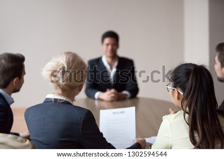 Rear view of hr managers group listen to african male applicant at job interview, recruiters employers talk to seeker making hiring decision meeting vacancy candidate, staffing recruitment concept