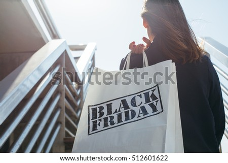 Rear view of incognito brunette holding Black Friday shopping bag while standing outdoors. Copy space