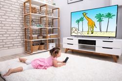 Rear View Of Innocent Girl Lying On Carpet Watching Cartoon On Television