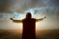 Rear view of Jesus Christ raised hands and praying to god with a sunrise sky background