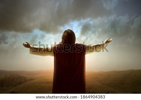 Rear view of Jesus Christ raised hands and praying to god with a sunrise sky background Stock photo ©
