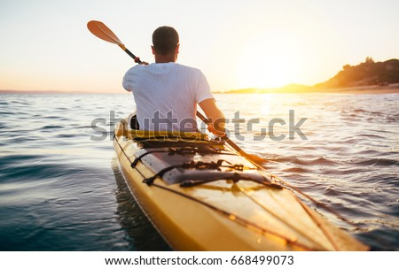 Rear view of kayaker man paddle kayak at sunset sea. Kayaking, canoeing, paddling