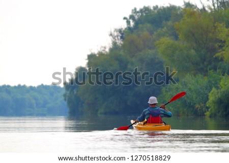 Rear view of kayaker man paddle yellow kayak on Danube river. Summer kayaking. Concept for adventure, travel, action, lifestyle