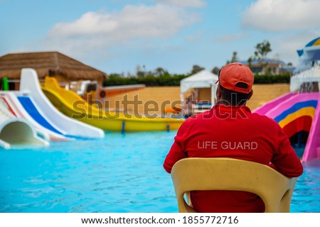 Rear view of lifeguard sitting on chair with rescue buoy at poolside. lifeguard looks at the children's pool. Vacation safety control. Babysitting on the water Foto stock ©