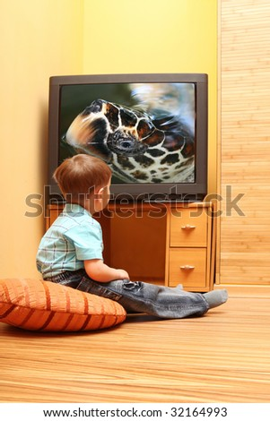 Rear view of little boy sitting on the floor and watching cinema on TV at home. TV screen - \