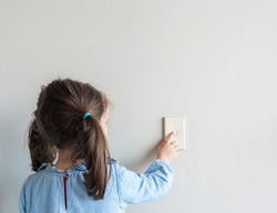 Rear view of little girl turning off Australian light switch on neutral wall background with copy space (selective focus)