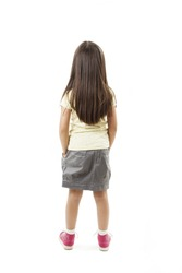 Rear view of little girl with long hair looking at wall. Isolated on white background.