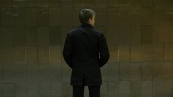 Rear view of lonely young man shot from behind at subway station add look at watch waiting for the train. Businessman at the station