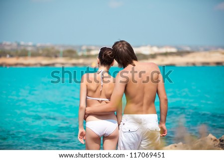 Rear view of lovely young couple standing on the beach facing sea