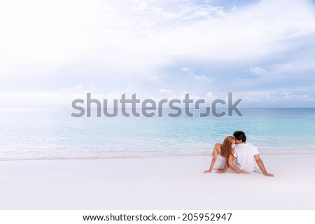 Rear view of loving couple relaxing on the beach, kissing outdoors, boyfriend with girlfriend enjoying summer holidays on luxury Maldives resort, love and romance concept