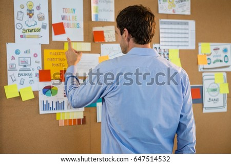 Rear view of male executive pointing at bulletin board in office Foto stock ©