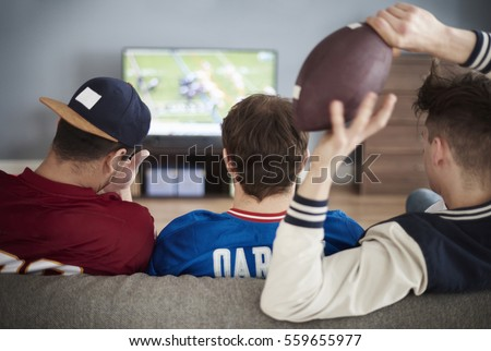 Rear view of male friends and tv on the background