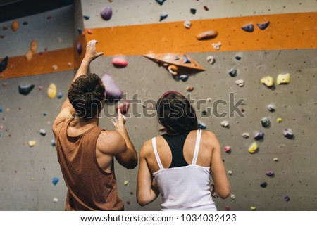 Rear view of male instructor giving instructions to a woman on wall climbing. Woman learning the art of rock climbing at an indoor climbing centre. #1034032423