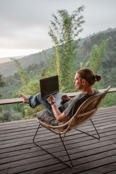 Rear view of male traveler blogger work remote on laptop computer while enjoying amazng nature moutains landscape view outdoors