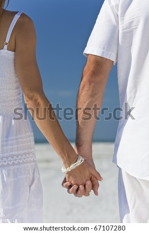 Rear view of man and woman romantic couple in white clothes holding hands and walking on a deserted tropical beach with bright clear blue sky