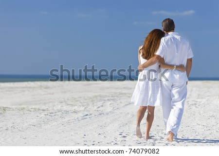 Rear view of man and woman romantic couple in white clothes walking on a deserted tropical beach with bright clear blue sky