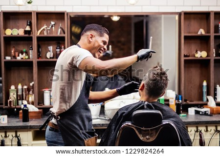 Rear view of man client visiting haidresser and hairstylist in barber shop.