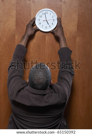 Rear view of man hanging clock on wall