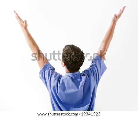 Rear view of man in blue shirt keeping his arms raised over white background