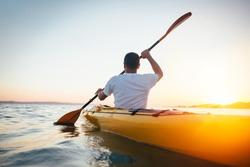 Rear view of man paddling canoe. Paddling, canoeing, kayaking