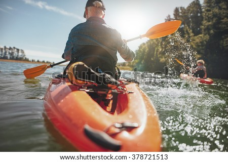 Rear view of man paddling kayak in lake with woman in background. Couple kayaking in lake on a sunny day.