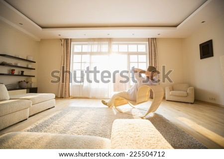 Rear view of man relaxing on modern chair at home