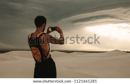 Rear view of man taking pictures of dramatic sky with his mobile phone during fitness training in desert. Fit man capturing cloudy sky pictures in his mobile phone while workout break.
