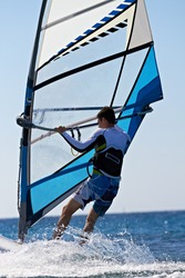 Rear view of man windsurfing in splashes of water closeup