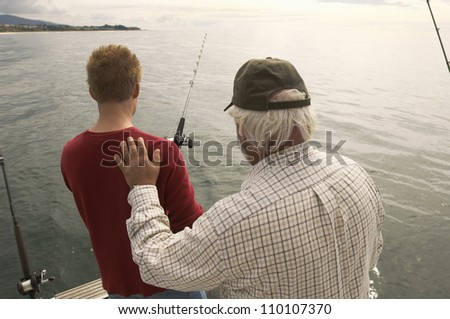 Rear view of man with grandfather fishing on yacht