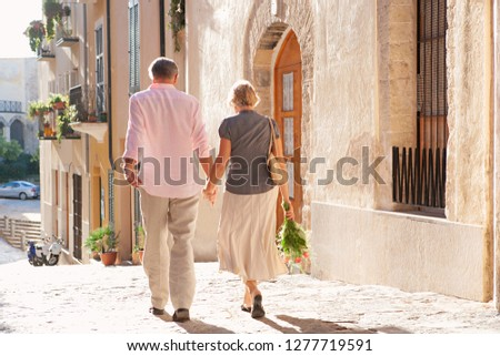 Rear view of mature tourist couple walking together holding hands and bouquet, sightseeing on retirement activities holiday, visiting city outdoors. Senior people vacation, travel leisure lifestyle.