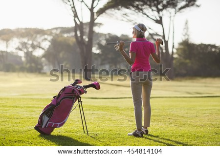 Rear view of mature woman holding golf club while standing on field