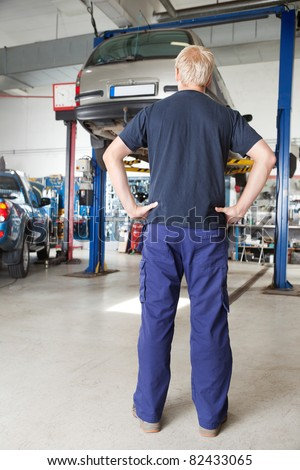 Rear view of mechanic looking at car in auto repair shop with hands on waist
