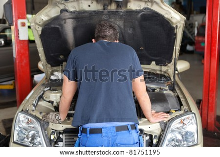 Rear view of mechanic working on a car in garage