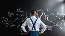 Rear view of middle-aged employee, trader standing near blackboard full of charts, while thinking of the new strategy of work. Horizontal shot. Concept of market analysis and business education