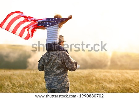 Rear view of military man father carrying happy little son with american flag on shoulders and enjoying amazing summer nature view on sunny day, happy male soldier dad reunited with son after US army