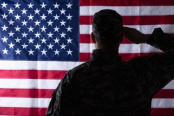Rear View Of Military Man Saluting Us Flag