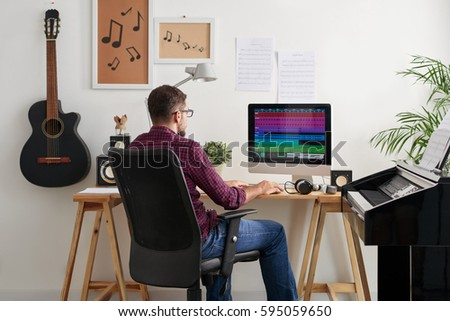 Rear view of mix engineer arranging music track