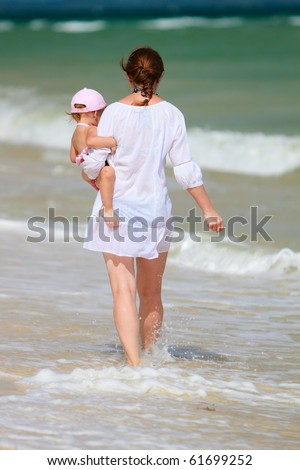 Rear view of mother holding baby in her hands walking along shore
