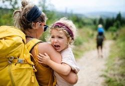 Rear view of mother with small crying daughter hiking outdoors in summer nature.