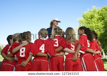 Rear view of multi ethnic football players with coach standing in the front