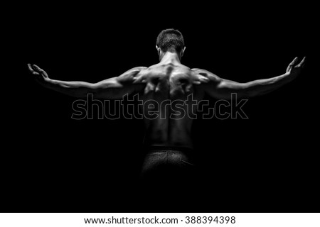 Rear view of muscular man with his arms stretched out #388394398