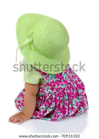 rear view of one year old baby girl toddler looking up leaning on one arm, on white background