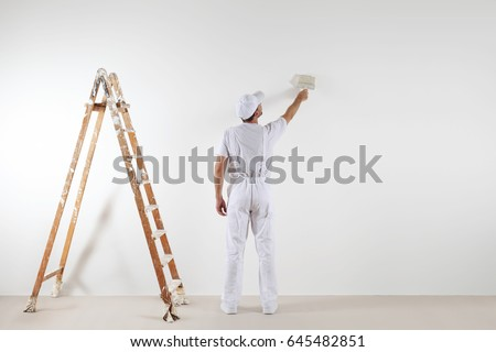 Rear view of painter man looking and painting blank wall, with paint brush and wooden ladder, isolated on white big space