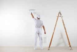 Rear view of painter man painting the wall, with paint roller and bucket, isolated on big empty space with wooden ladder
