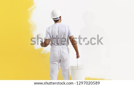 Rear view of painter man painting the wall, with paint roller and bucket, isolated on big empty copy space template Stockfoto ©