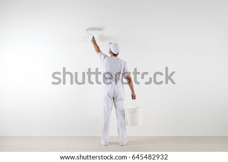 Rear view of painter man painting the wall, with paint roller and bucket, isolated on big empty space