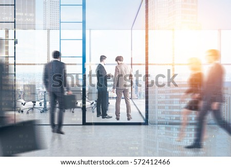 Rear view of people in a meeting room with glass walls. Reception counter is to the right of it. 3d rendering. Toned image. Double exposure. #572412466