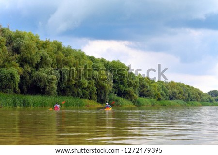 Rear view of people in two kayaks. Kayaking on summer Danube river together with green trees in the background. Concept of tourism and outdoor activities on the water