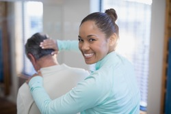 Rear view of portrait of smiling female therapist giving neck massaging to senior male patient at hospital ward